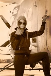 Beautiful girl in jacket standing next to war aircraft. Retro photo.