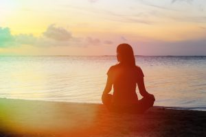 young woman meditation on sunset beach
